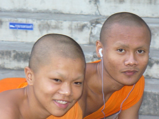 two young monks, one with Apple earbuds in, at Wat Suan Dok in Chiang Mai