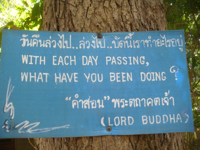 "A sign at Wat Umong, the nearby Forest Temple, that has a quote from Buddha that says in English and Thai: ""With each day passing, what have you been doing?"""