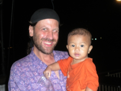Dan with a 1-year-old Thai baby playing in the rain while his parents tend their outdoor restaurant in Pitsanulok