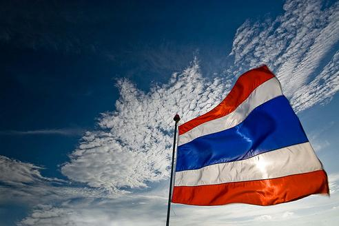 Thai flag fluttering against a blue sky with white clouds