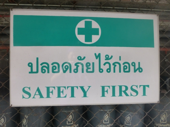 Safety First in Thai and English with a green cross logo